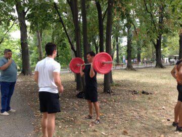 Млади щангисти с открит урок по вдигане на тежести под открито небе в парка